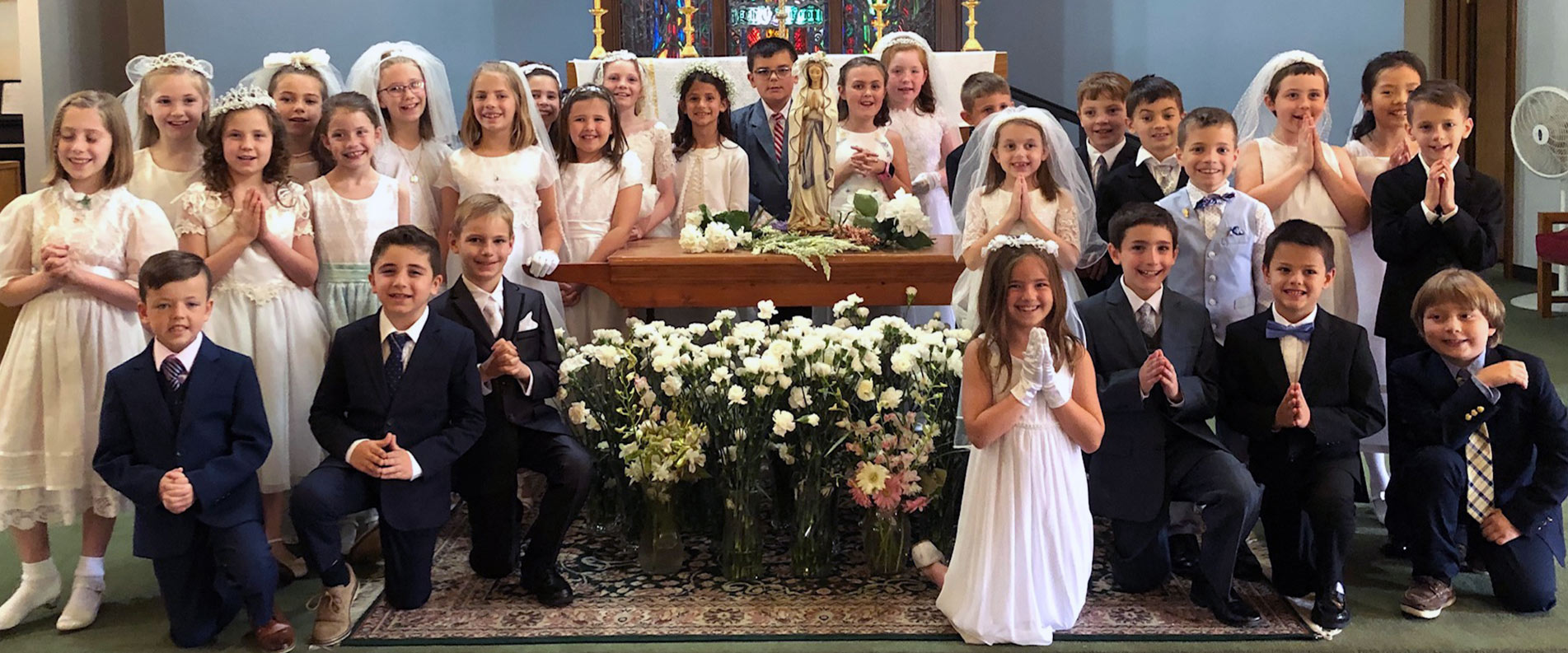Second Graders in First Communion clothing posing after May Crowning